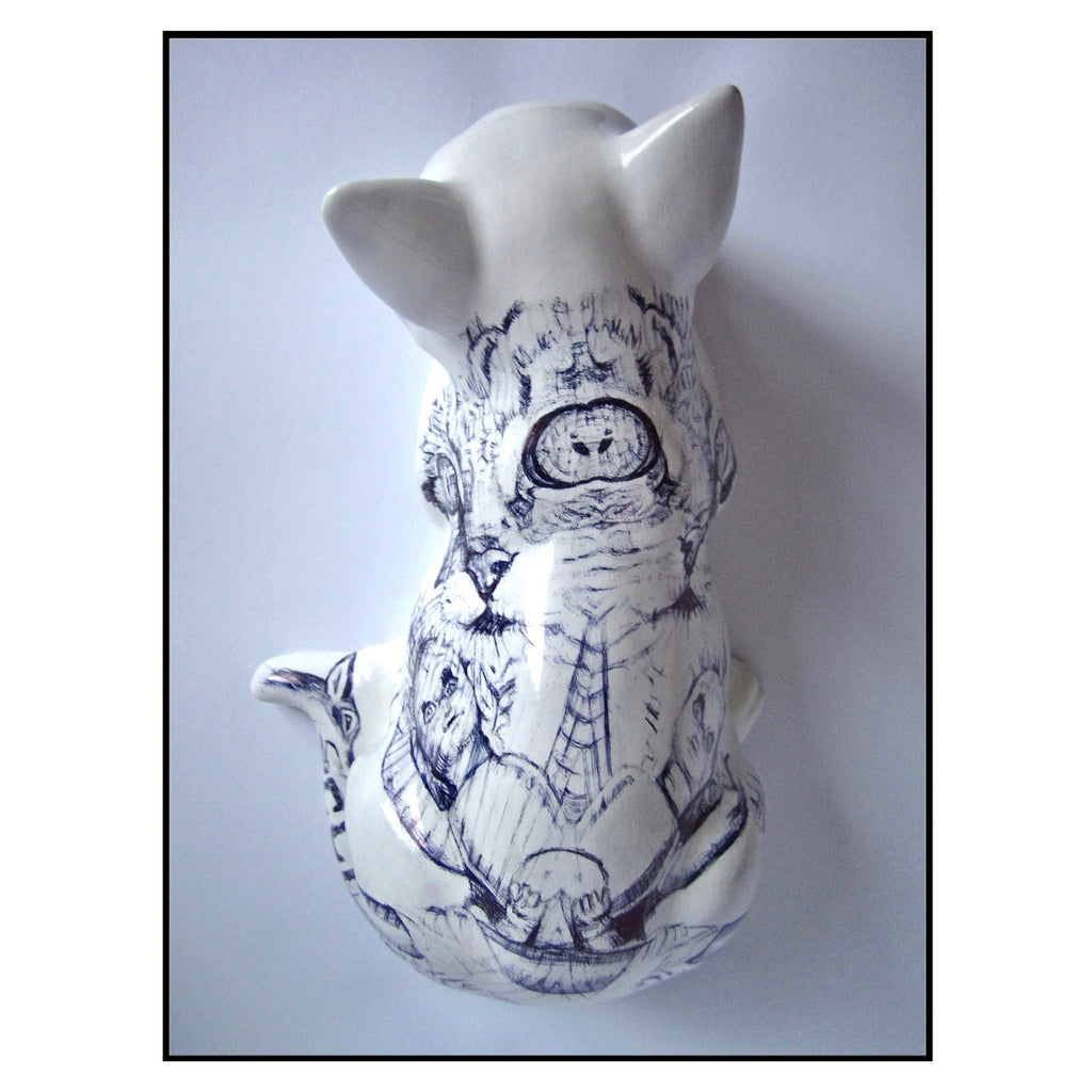 China cat figurine with a Biro drawing of cats and dolls