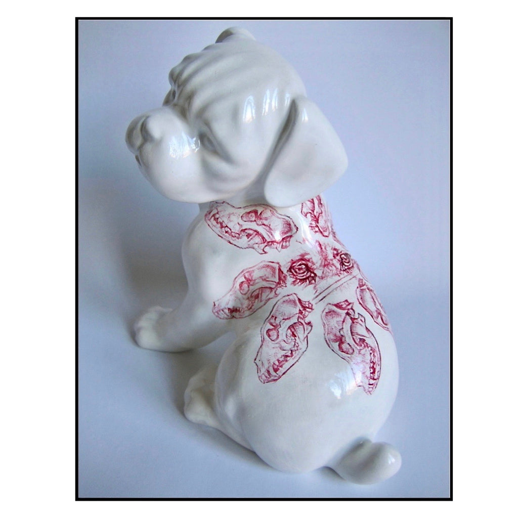 China puppy figurine with a red Biro drawing of a dog skulls pattern