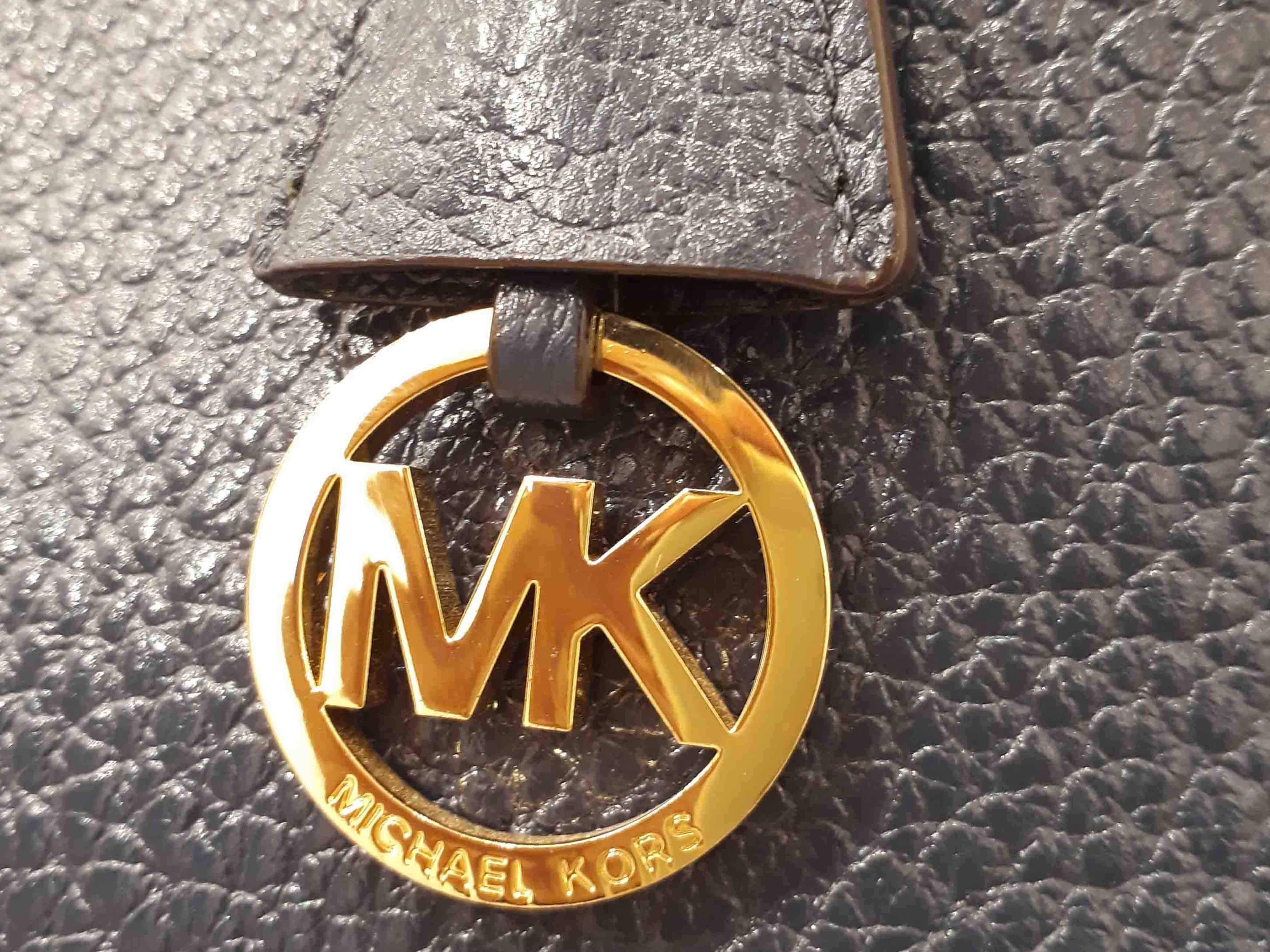c5a66f7f9b2a64 The letters 'MK' are placed very close to each other. The hanging charm is  suspended at the end of a matching leather strap or chain and appears solo  ...