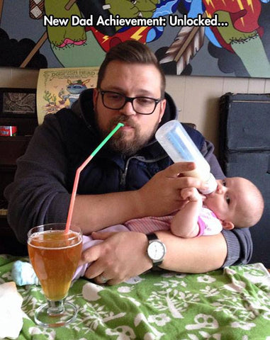 Dad drinking beer while feeding baby