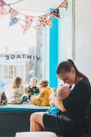woman nursing baby in black dress at cafe while toddlers play in window