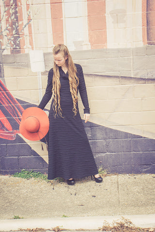 Iris - long black ribbed sweater dress with cowl neckline matched with rust tassle hat