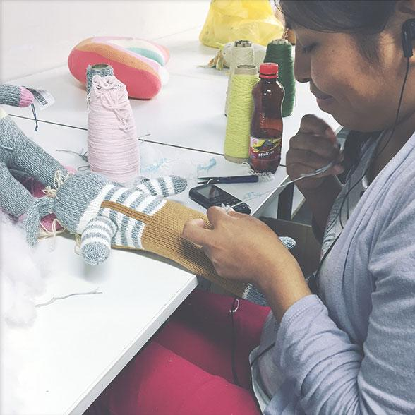 A woman sewing a stuffed doll.