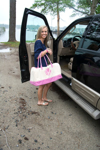 Model carrying a monogrammed pink gingham duffle bag