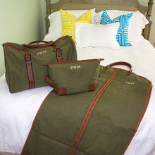 Personalized dopp kit, duffle bag and suit bag on a bed