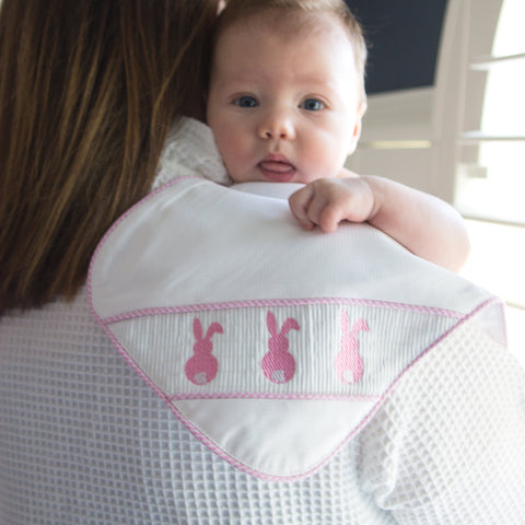 Lifestyle image of our Pink Bunny Smocked Burp Cloth