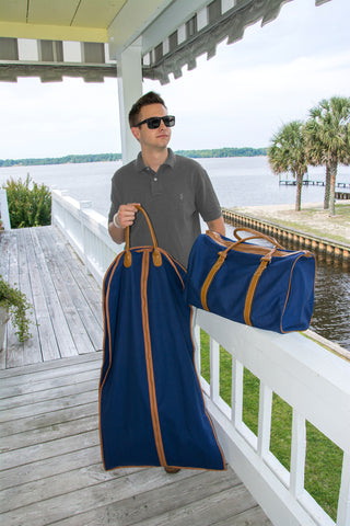 Young man carrying his suit bag and duffle bag