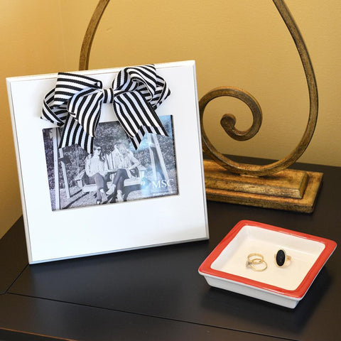 White frame with black & white stripe bow at the top of the frame, holds 4 x 6 on a desk