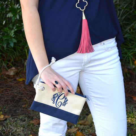 Model holding a monogrammed navy rope pouch with the string around her wrist