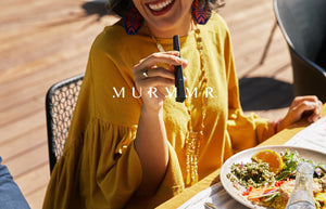 Murmmr hero image. Woman enjoying Murmmr product with friends outside during a meal.