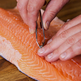 Pin-boning a fillet of salmon by hand