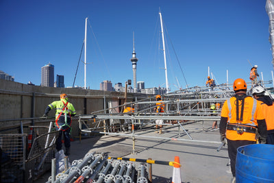 construction workers on roof overlooking auckland sky tower