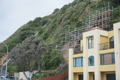 scaffolding on mountain and yellow house at front