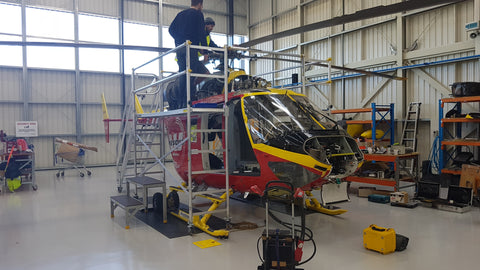 rescue helicopter being worked on with scaffolding