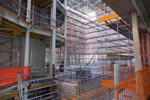 inside of building with scaffolding and orange restrictions