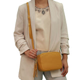 Mustard real soft leather compact cross body bag with leather tassel attached to zipper closure