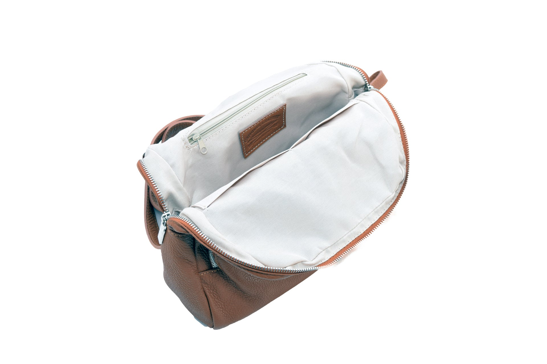 Tan leather backpack with three external compartments and silver hardware