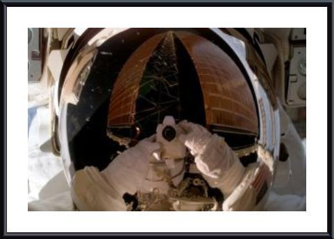 Astronaut uses a digital still camera to expose a photo of her helmet visor during a spacewalk., framed black metal, white matte