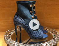 blue suede peep-toe booties with laser cut overlay design and brass bead details