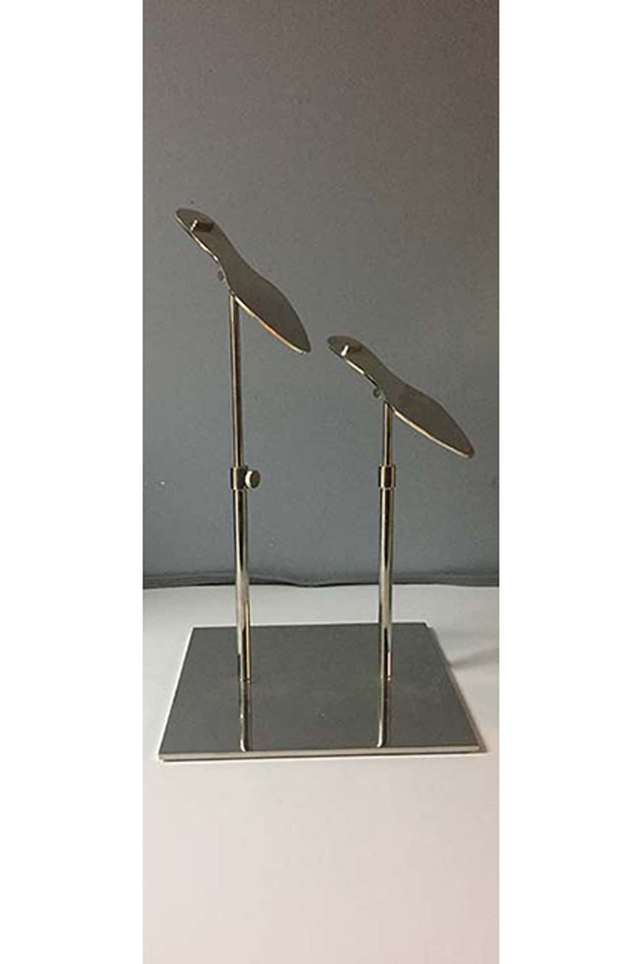 metal plated shoe stand with two uneven shoe holders and a square base