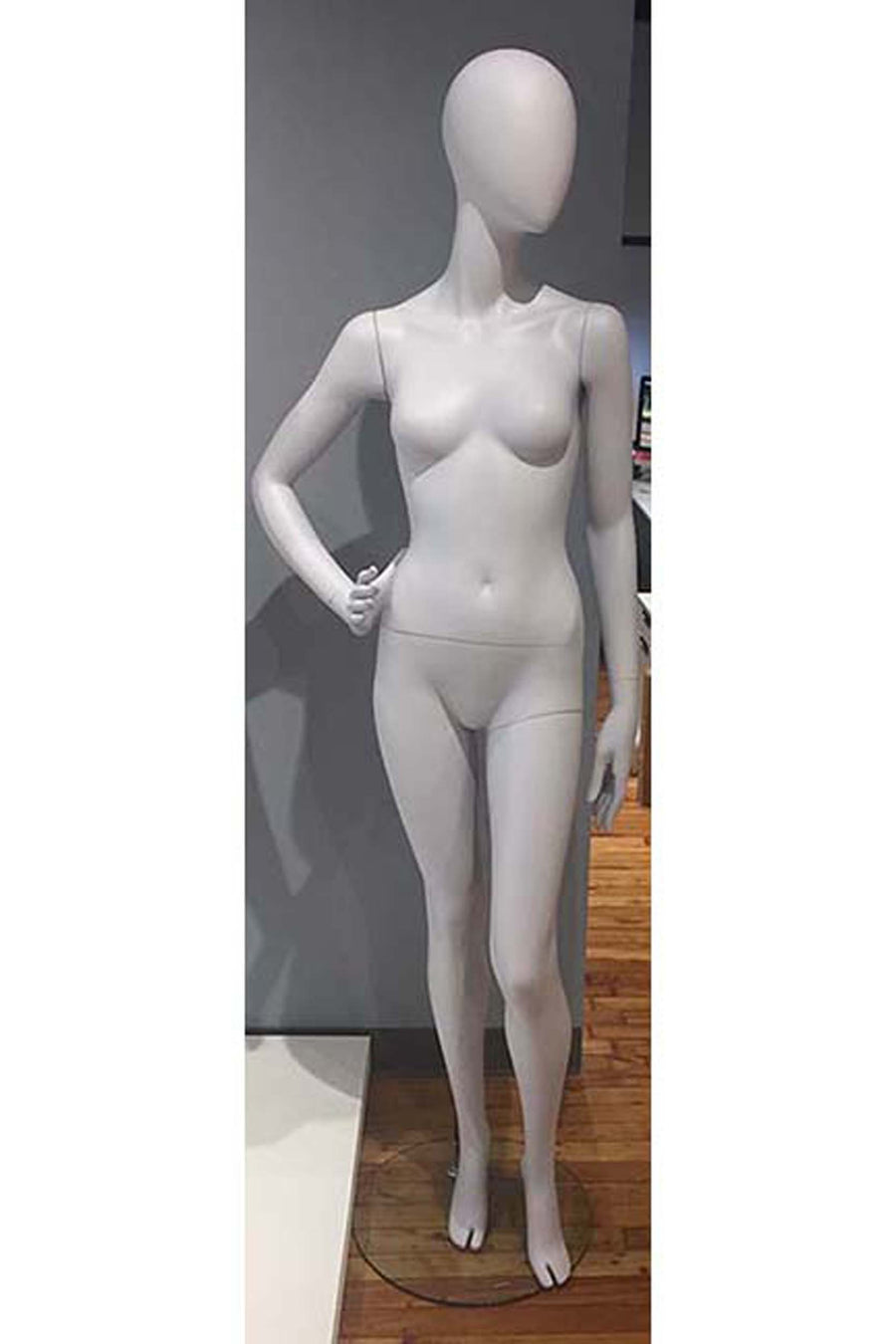 pale gray female mannequin with blank face and right hand on hip