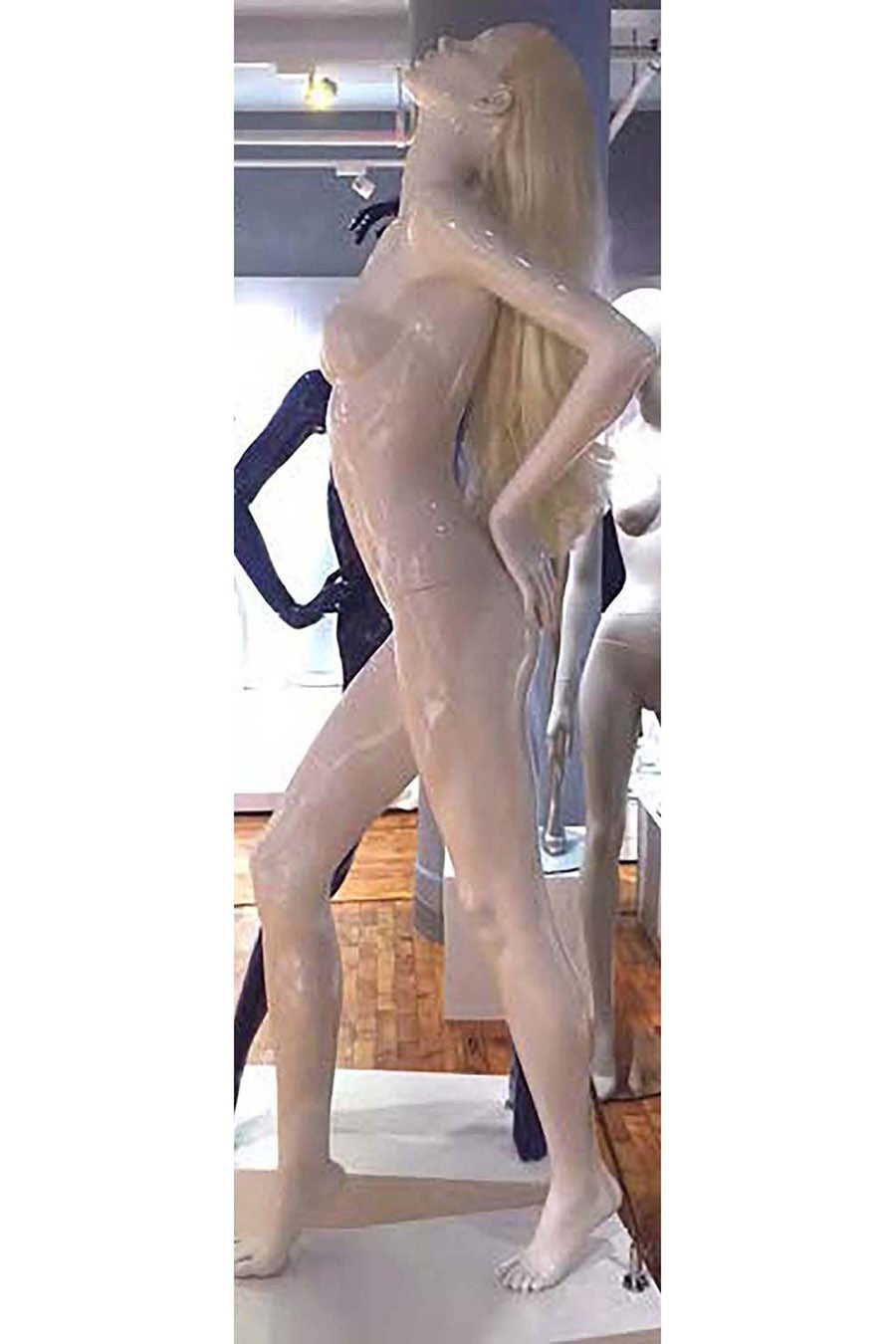 signal white female mannequin with head tilted back, hands on hips with back arched, and right leg stepping forward