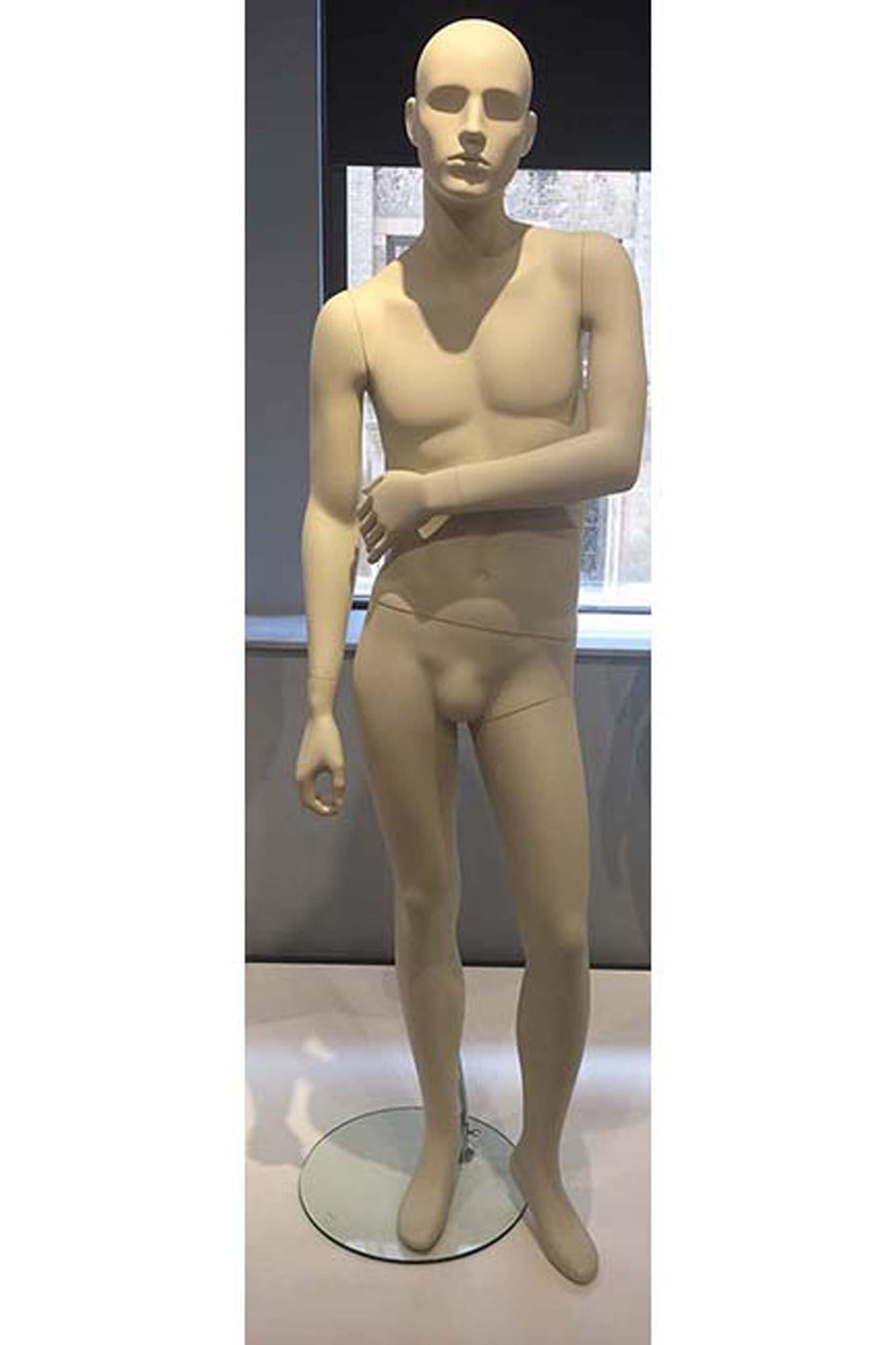 oyster white male mannequin with left hand touching right arm
