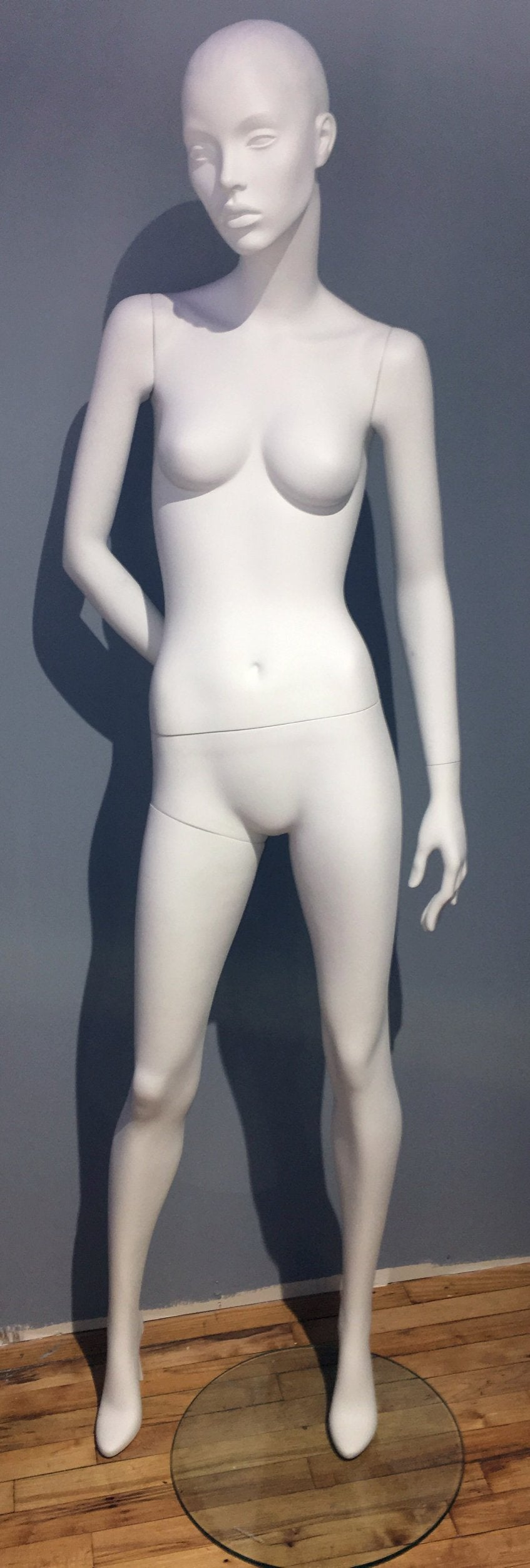 pure white female mannequin with legs shoulder width apart and right hand behind back