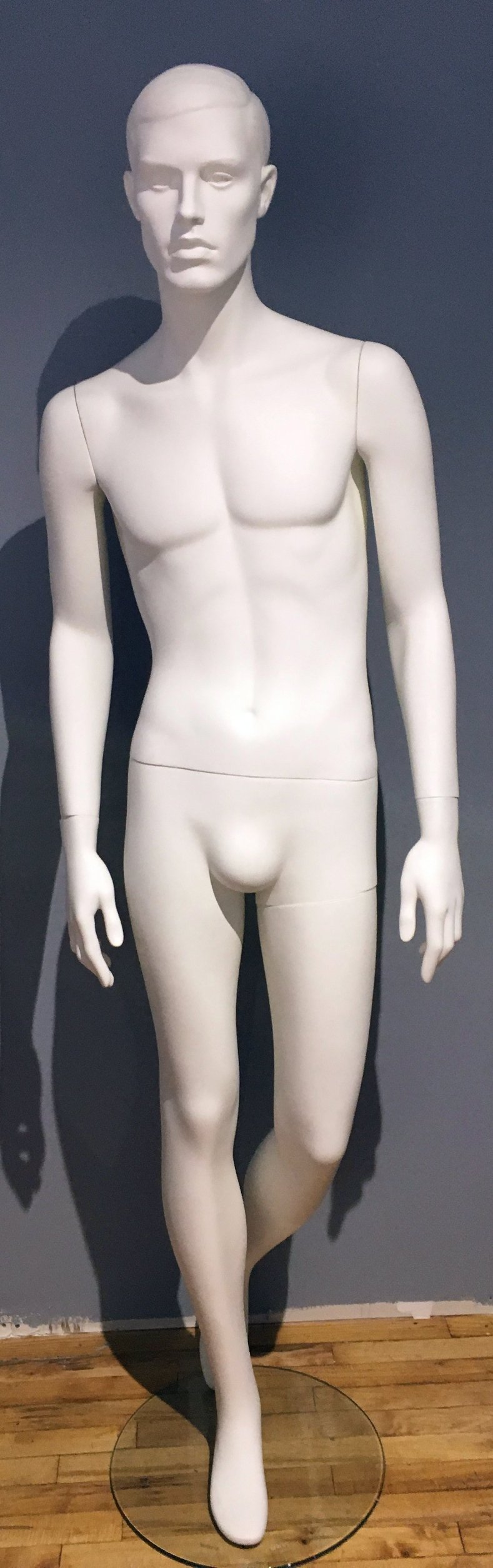 pure white male mannequin with arms at sides and left leg slightly bent behind right