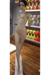 alabaster female mannequin with arms in motion and right leg in front of left