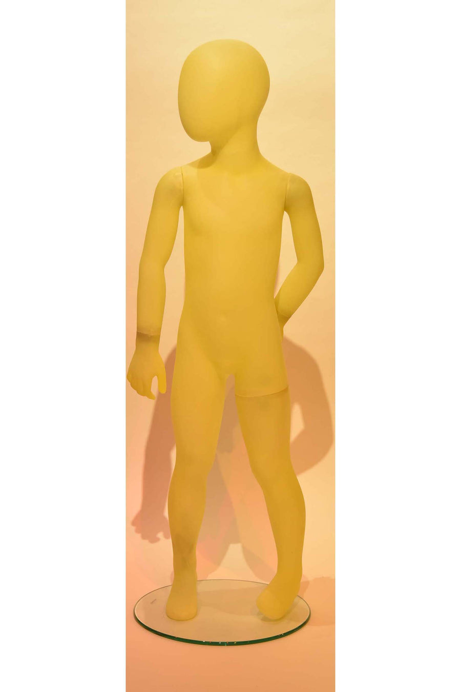 frosted yellow kid mannequin with left hand on hip