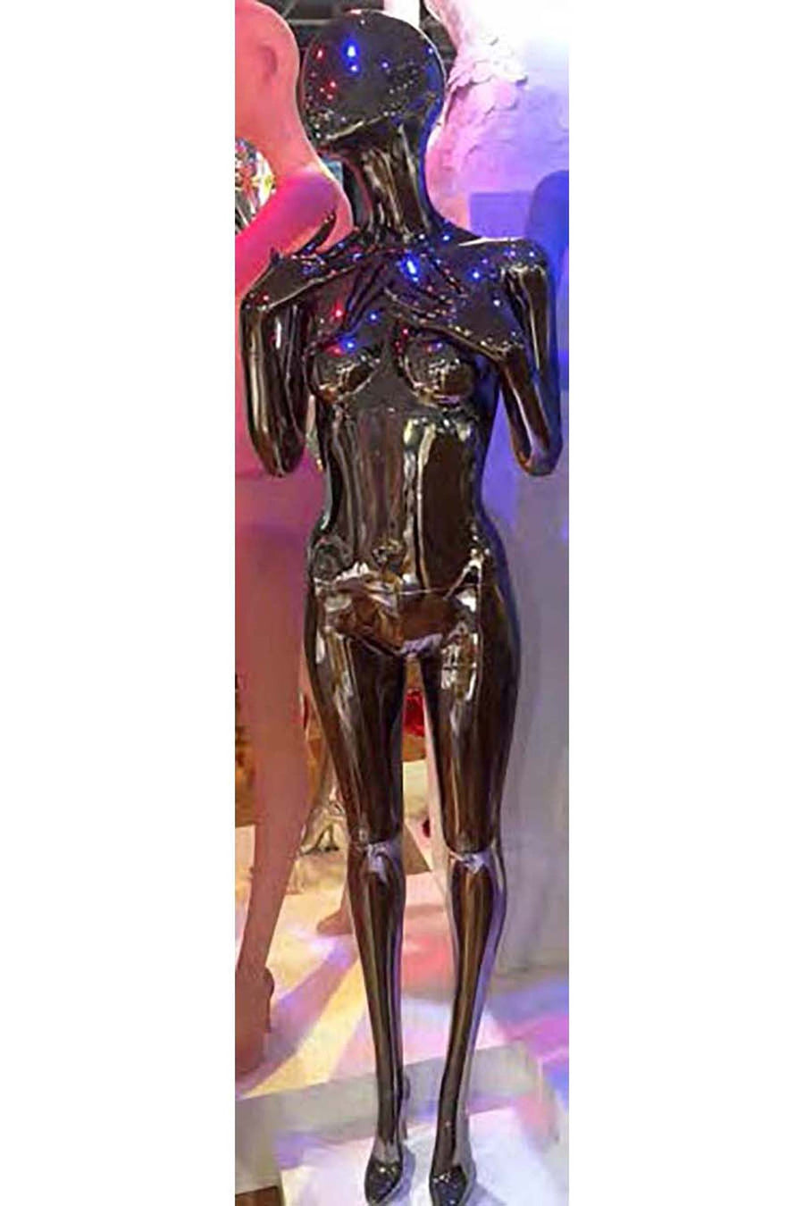 black chrome female mannequin with arms bent and hands near shoulders