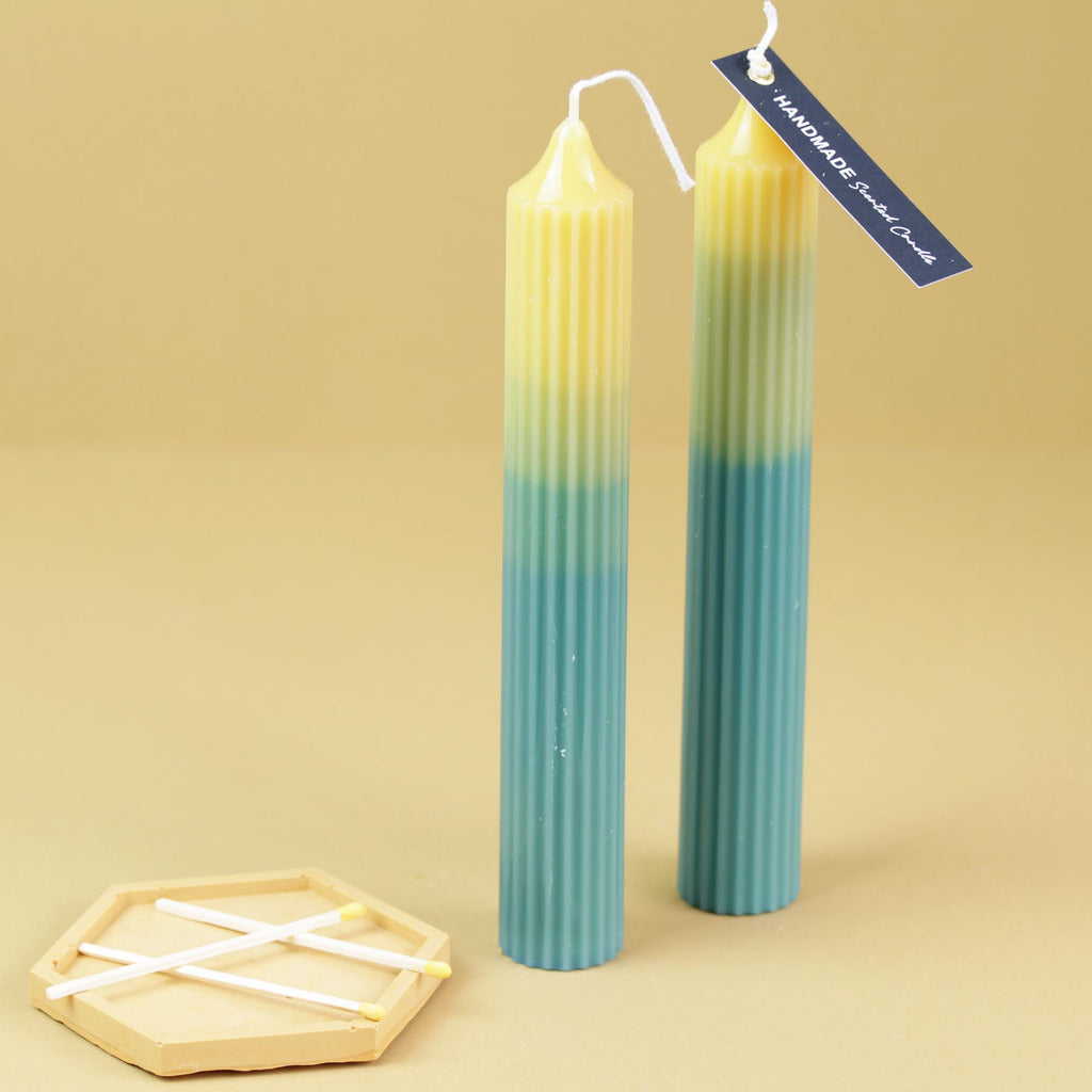 An Ombre Pillar Candle with Ribbed Detail.