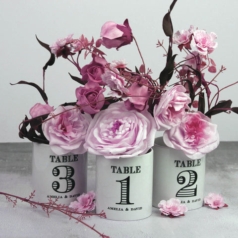 Personalised vintage style table numbers on pots.