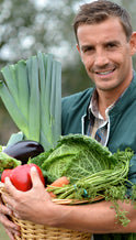 man holding a basket of vegetables and smiling