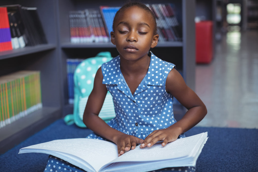 Young black girl reading braille book in school library
