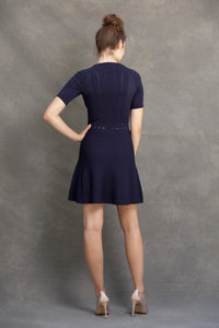 Alexa Fit and Flare Dress - VIAVAI FASHION  Back view of a brunette model with her hair up in a messy bun, wearing a fit andf flare knit dress in Navy color with beautiful textures and open knit details