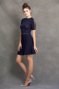 Alexa Fit and Flare Dress - VIAVAI FASHION  Profile view of a brunette model in nude heels, with her hair up in a messy bun, wearing a fit andf flare knit dress in Navy color with beautiful textures and open knit details