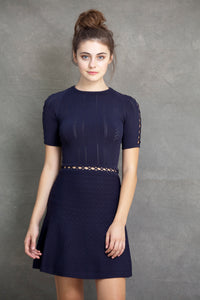 Alexa Fit and Flare Dress - VIAVAI FASHION  A brunette model with her hair up in a messy bun, wearing a fit andf flare knit dress in Navy color with a beautiful texture and open knit details