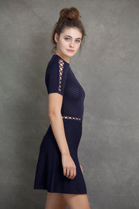 Alexa Fit and Flare Dress - VIAVAI FASHION  Profile view of a brunette model with her hair up in a messy bun, wearing a fit andf flare knit dress in Navy color with beautiful textures and open knit details
