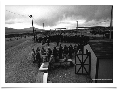 Question Mark by Nicholas Price.  A group of U.S. Air force men and women line up to receive ammunition for a training exercise before deployment.