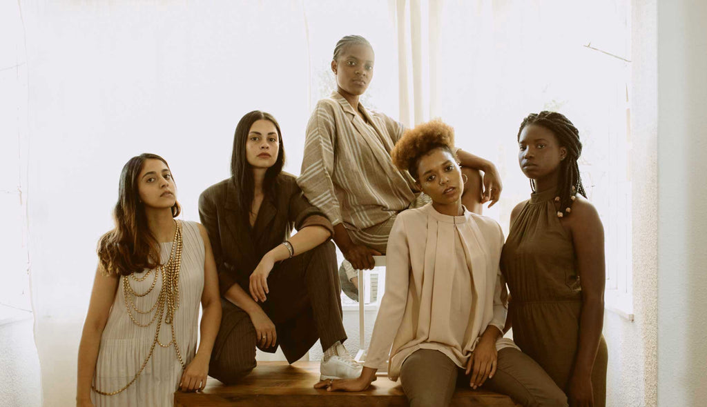 Five BIPOC women sitting on a brown table. Allyship for fashion brands