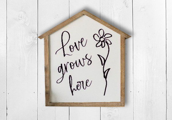 """Love Grows Here"" wood framed sign in shape of a house"