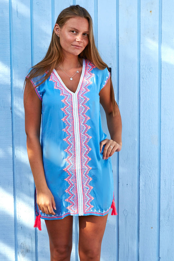 Kaftan style beach tunic in light blue with orange and white detailing.  Short cap sleeves.  Available in 2 sizes
