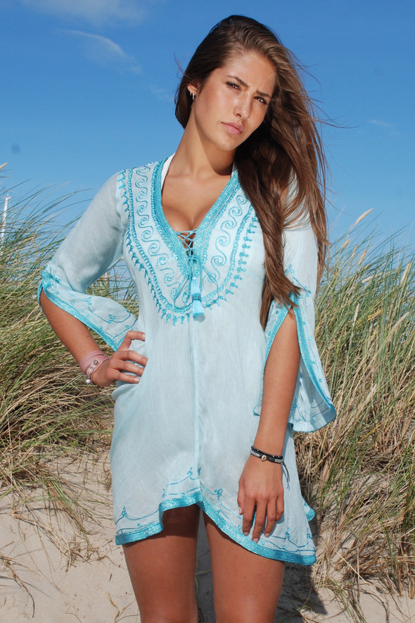Kaftan dress in turquoise with a turquoise shimmer embroidery to neckline.  Above the knee length and a plunging sexy deep neckline