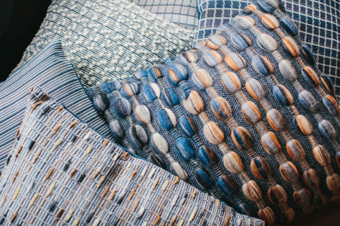 Piles of contemporary, hand-woven cushions by Cassandra Sabo