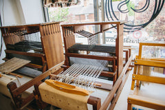 Harris tables looms with white warp set up for weaving