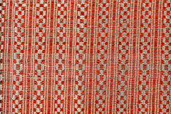 Patterned handwoven fabric featuring hand-dyed red yarn with gold