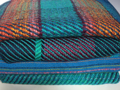 Stacks of handwoven cloth with stripe patterns in blue, orange and green
