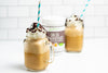 Chai Frappuccinos in mason jars with straws next to Primal Kitchen Chai Collagen Keto Latte Drink Mix
